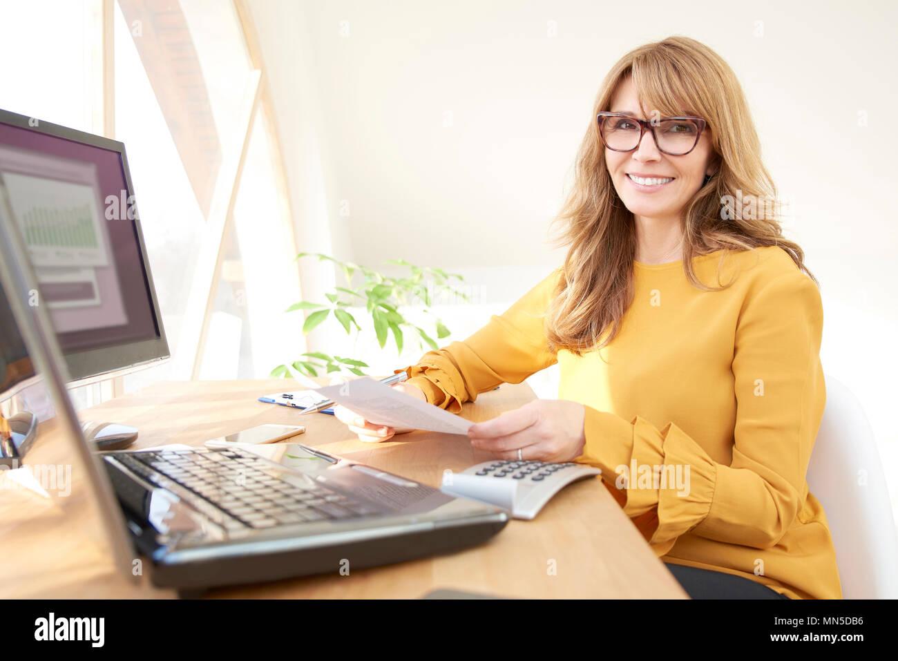Di mezza età imprenditrice executive seduti al computer e laptop e facendo alcuni documenti. Home office. Foto Stock