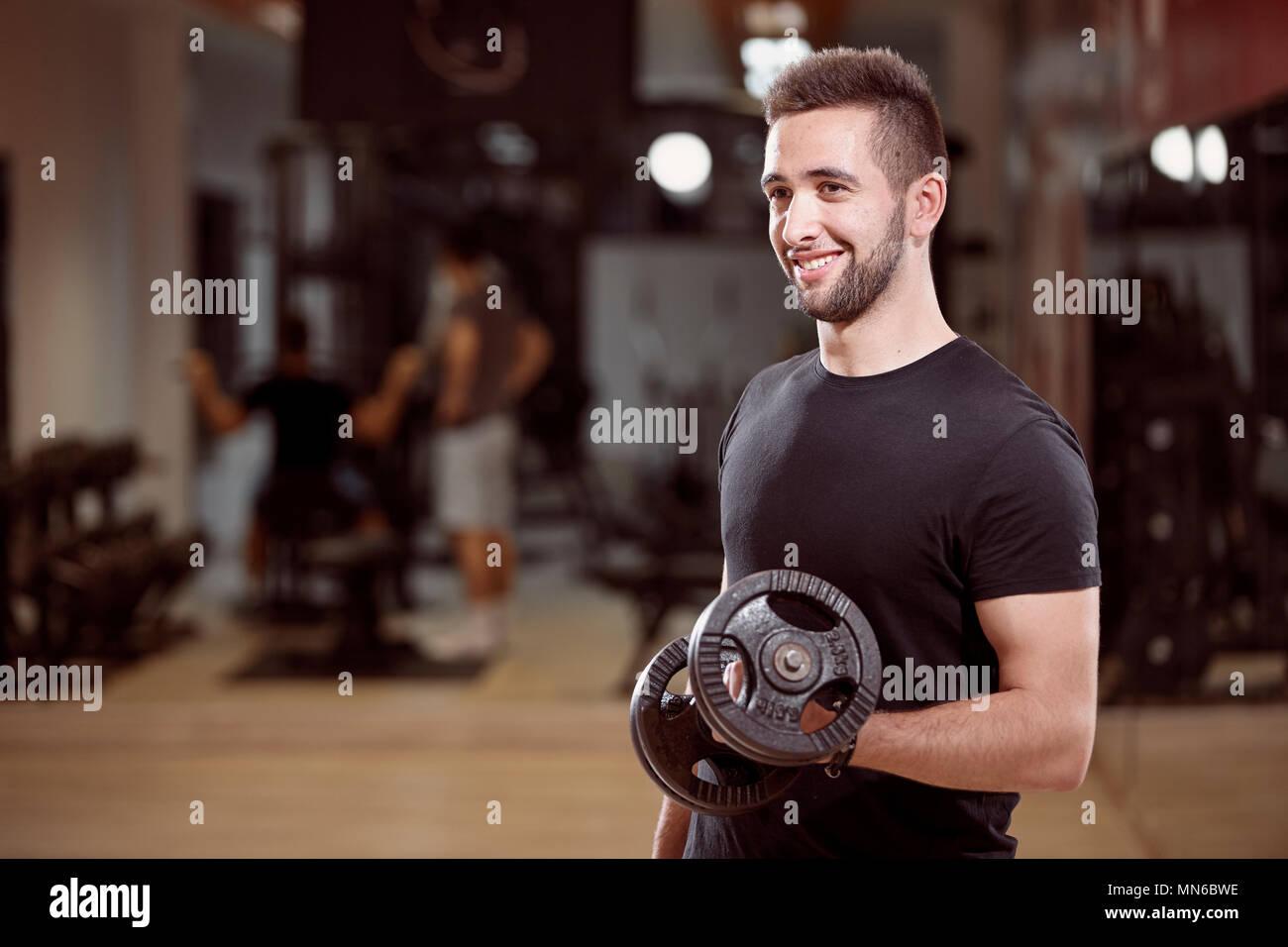 Un giovane uomo, media ordinaria cercando un braccio dumbell esercizio, sorridente, in palestra. Irriconoscibile gruppo di persone dietro a. Immagini Stock