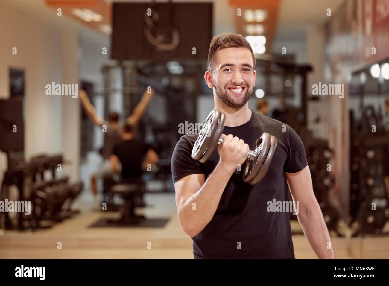 Un giovane uomo, media ordinaria cercando un braccio dumbell esercizio, smirking, in palestra. Irriconoscibile gruppo di persone dietro a. Immagini Stock