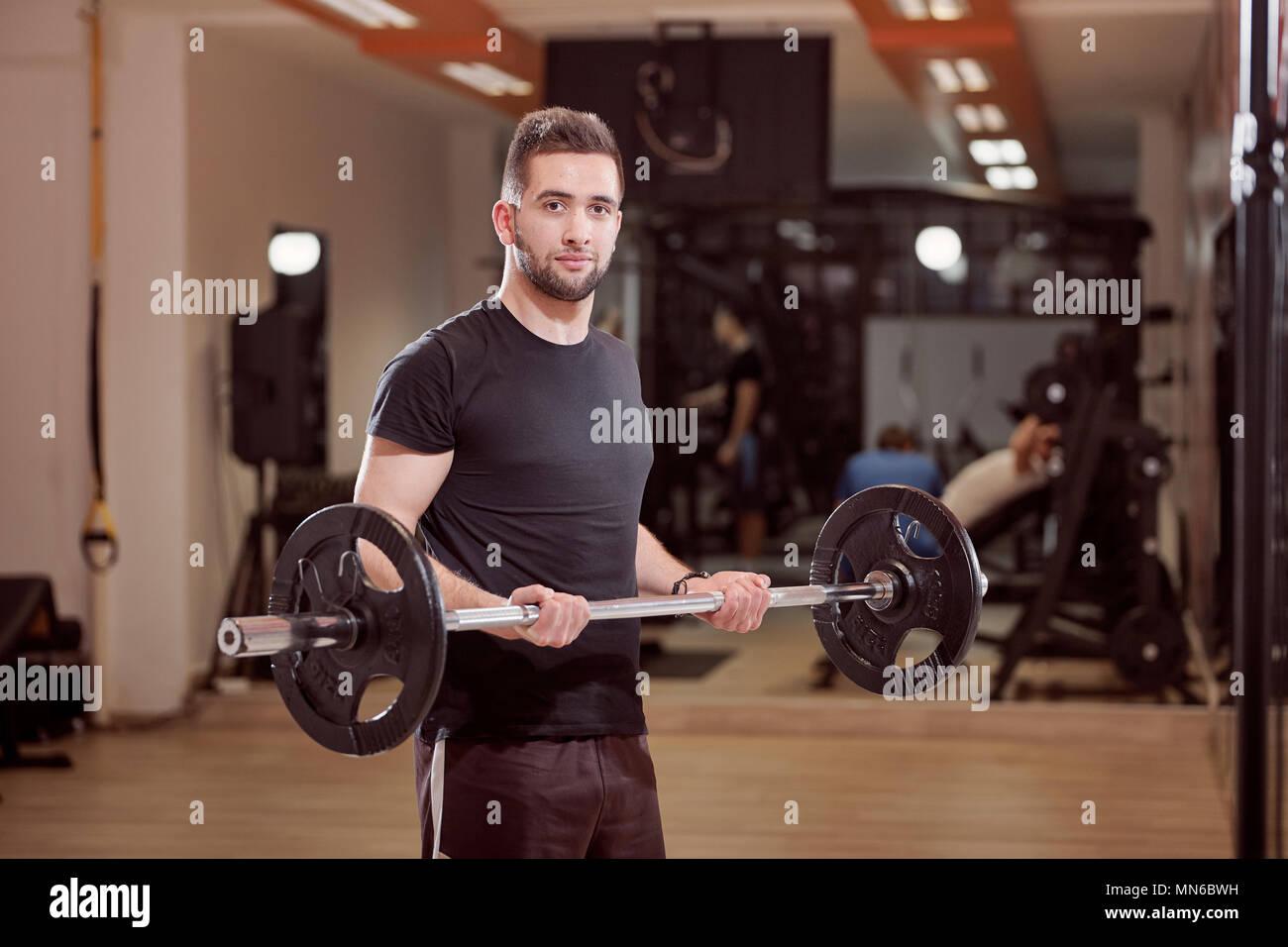 Un giovane uomo che pongono, media ordinaria cercando, tenendo barbell con pesi, esercizio in palestra. Irriconoscibile la persona dietro (al di fuori della messa a fuoco). Immagini Stock