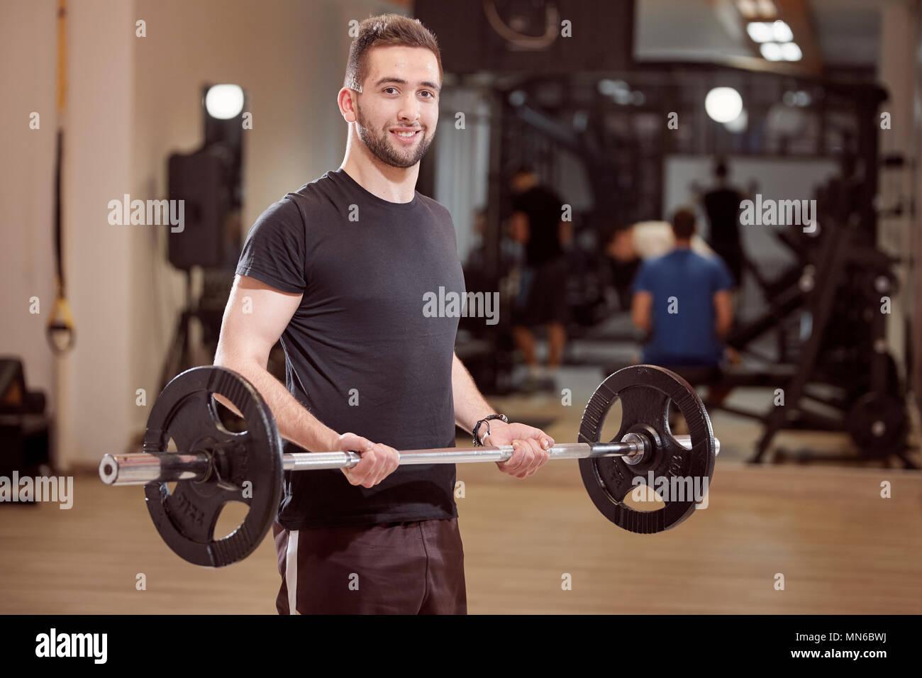 Un giovane uomo che pongono, ordinario, media cercando, tenendo barbell con pesi, esercizio in palestra. Irriconoscibile la gente dietro (al di fuori della messa a fuoco). Immagini Stock