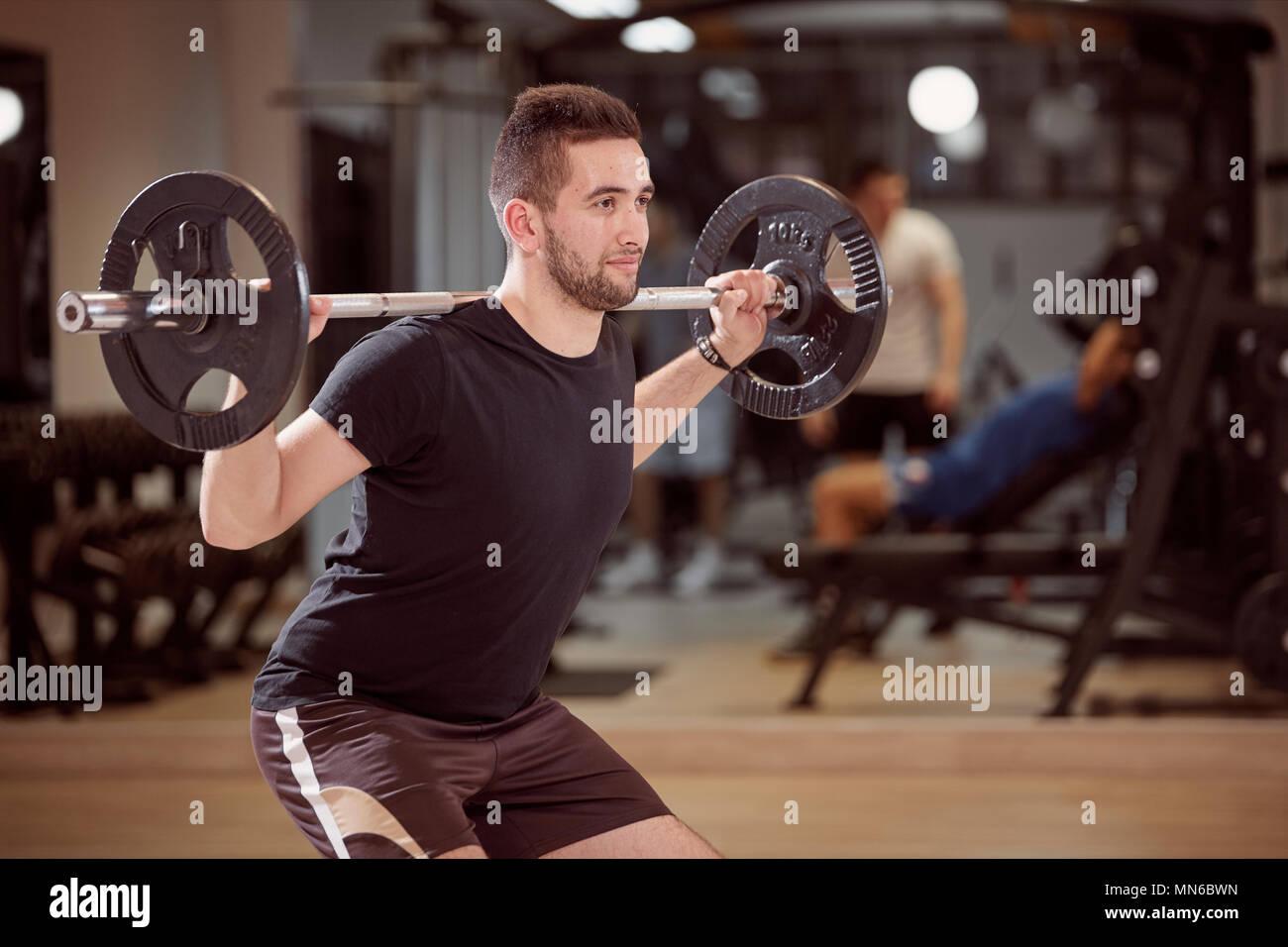 Il corpo superiore shot, esegui uno squat esercizio, giovane azienda barbell con pesi sulle spalle indietro. Irriconoscibile la gente dietro in palestra (al di fuori della messa a fuoco) Immagini Stock