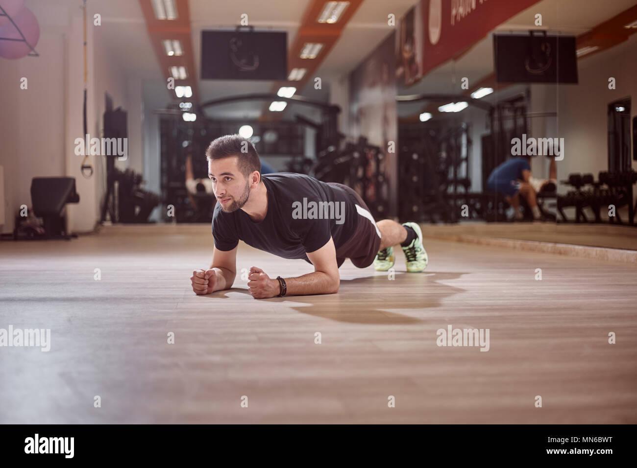Un giovane uomo che guarda lontano, plank esercizio, palestra pavimento, irriconoscibile persone dietro (al di fuori della messa a fuoco). Immagini Stock