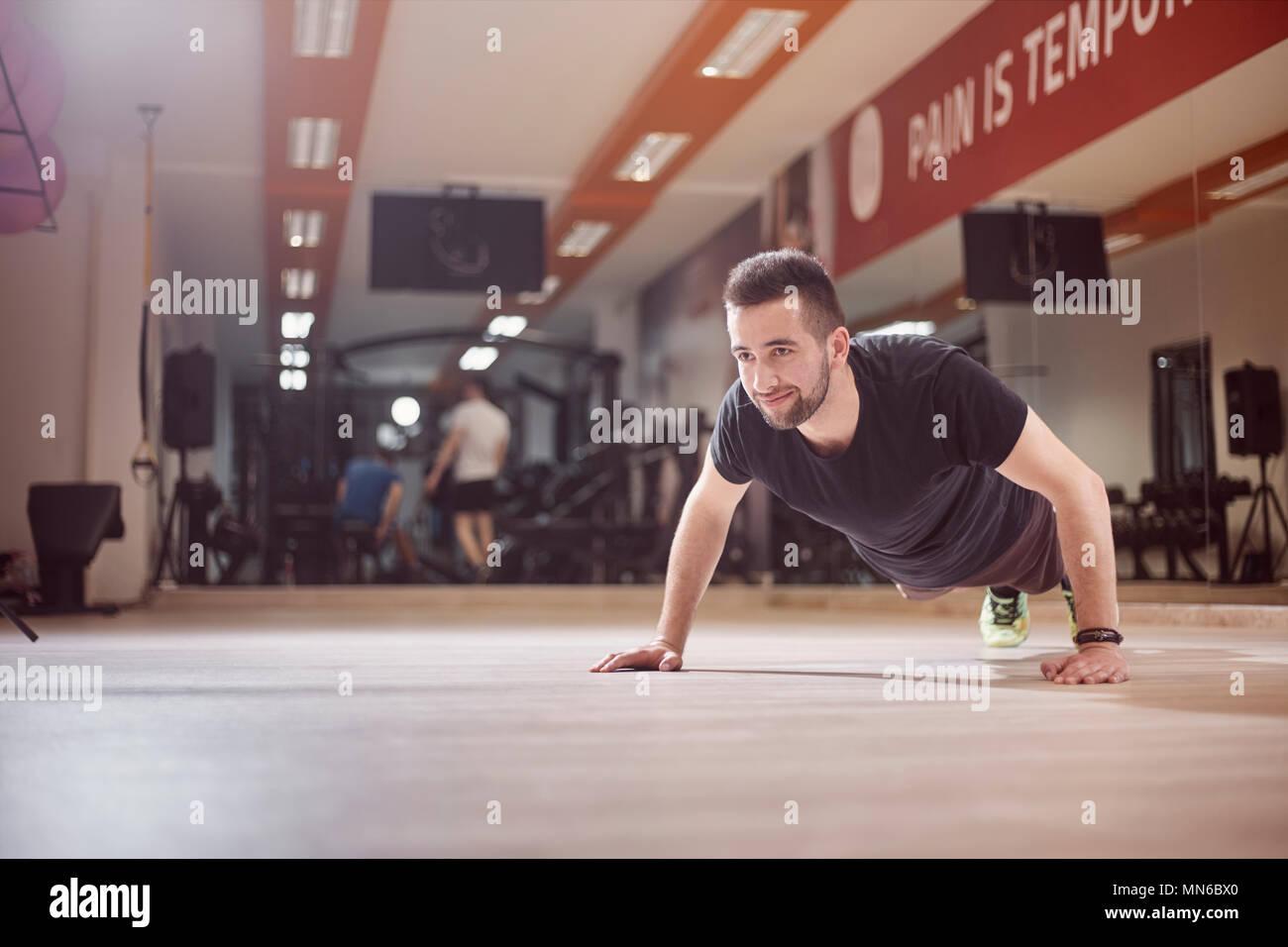 Un giovane uomo, push-up esercizio, palestra pavimento, irriconoscibile persone dietro (al di fuori della messa a fuoco). Immagini Stock