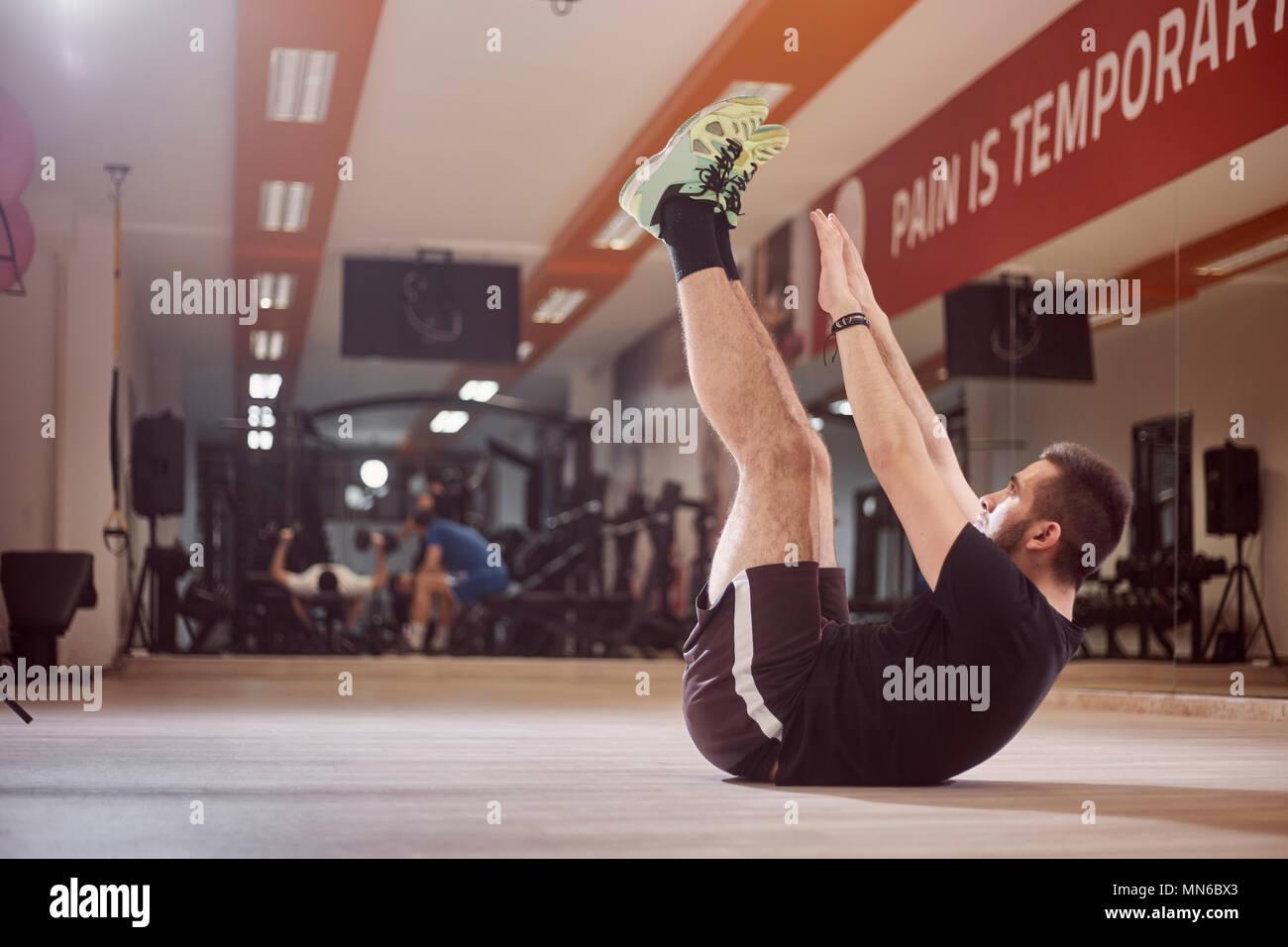 Un giovane uomo, ordinario uomo medio, esercizio abs, braccia estese alta in aria, seduto sul pavimento, in palestra. Irriconoscibile la gente dietro (al di fuori della messa a fuoco). Immagini Stock