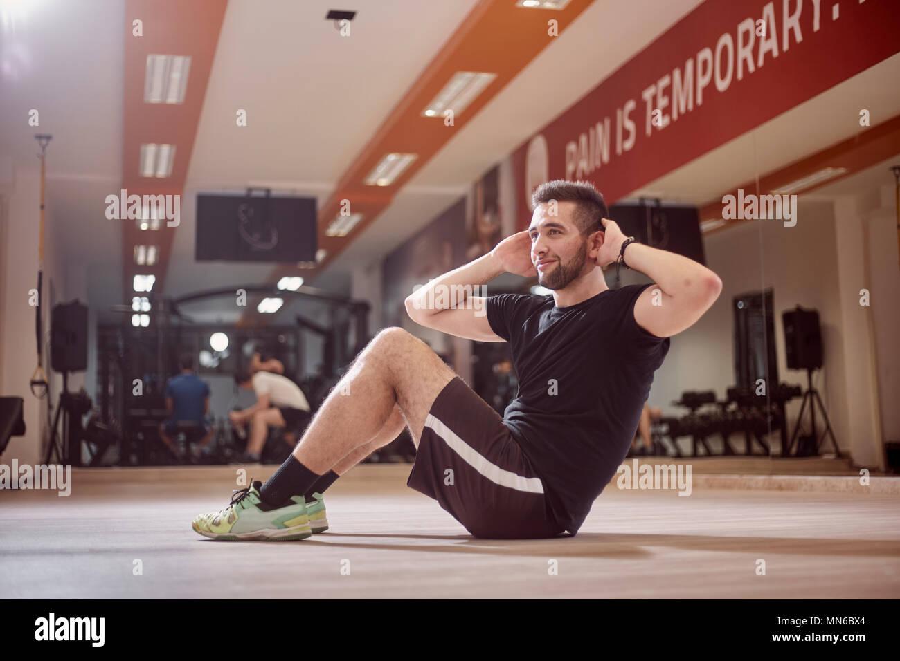Un giovane uomo, ordinario uomo medio, esercizio abs, lateralmente, seduto sul pavimento, in palestra. Irriconoscibile la gente dietro (al di fuori della messa a fuoco). Immagini Stock