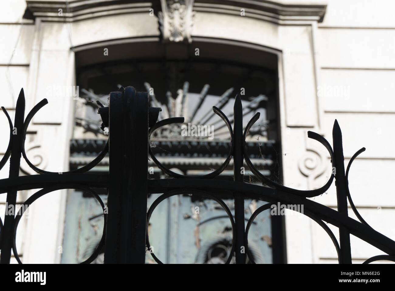 Guarda dall'esterno dietro il cancello di ferro antico e scolpiti in stile gotico Immagini Stock