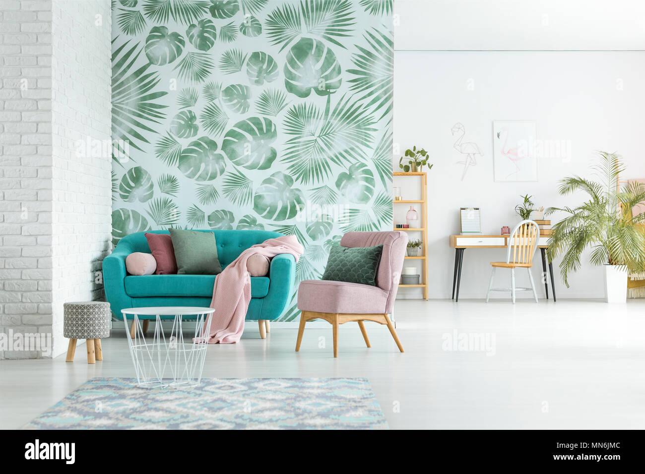 Poltrona rosa e blu divano con coperta in luminoso soggiorno con