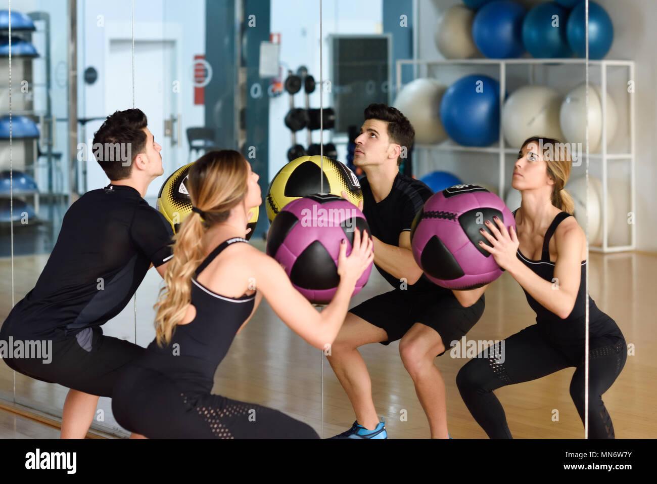 36a05ac2af23 Uomo e donna fitballs sollevamento in palestra. I giovani indossano abiti  di abbigliamento sportivo di fronte a uno specchio.