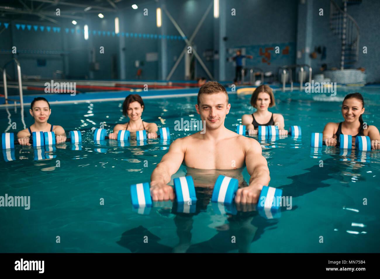 ce6726901e7c Femmina di aerobica in acqua di gruppo e formatore maschio fare esercizio  con manubri sulla formazione in piscina. Allenamento fitness, sport d'acqua