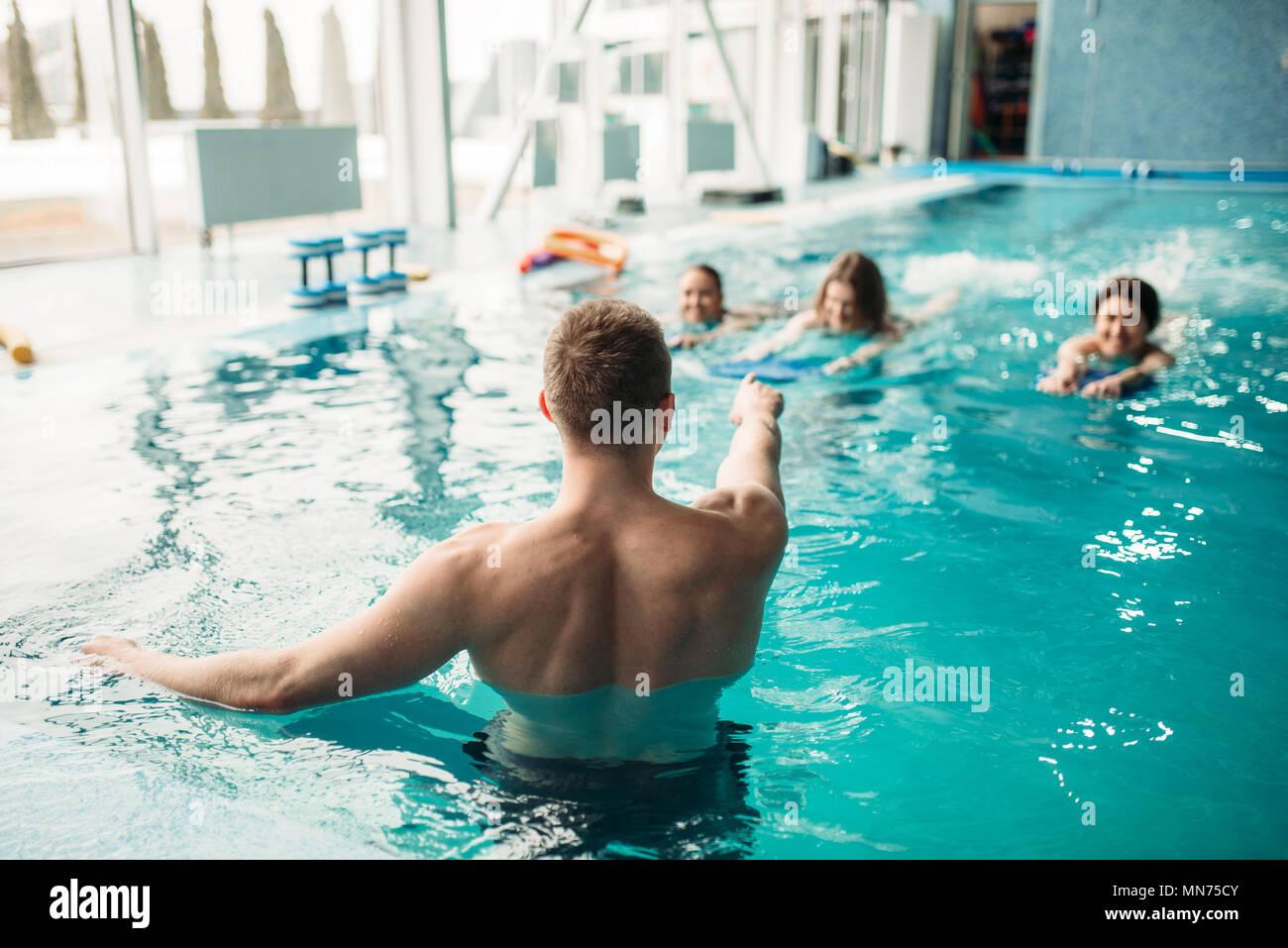 d498d7cef523 Istruttore maschio lavora con femmina sulla classe di allenamento in piscina.  Corsi di aerobica in acqua formazione, sport d'acqua