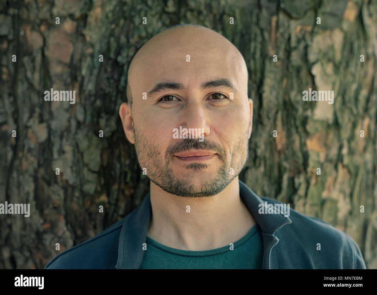La faccia di un barbuto grave uomo calvo nel parco. Ritratto di un uomo di mezza età. Foto Stock