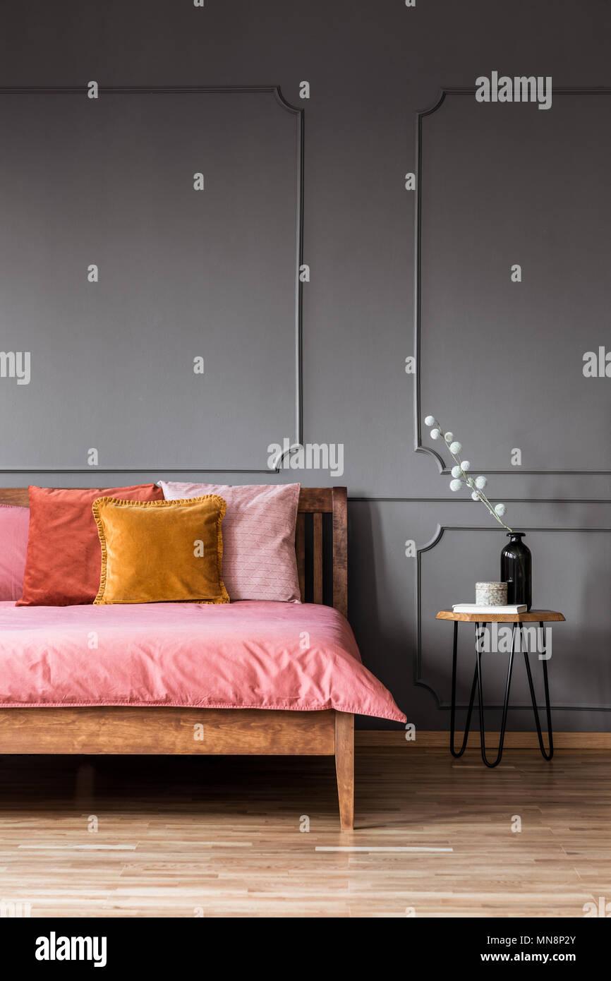 Cuscini colorati in rosa letto in legno nella camera da ...