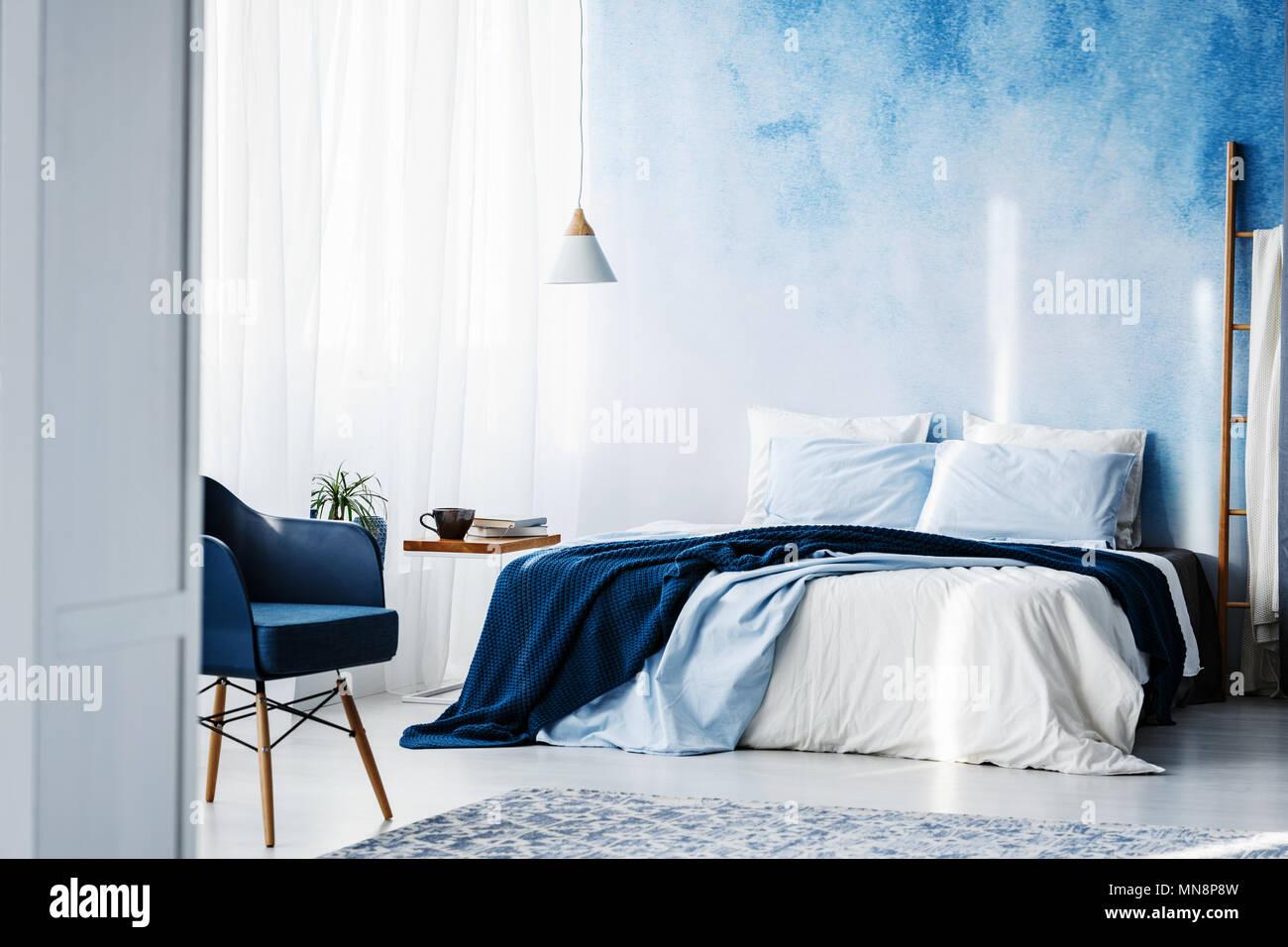 Navy Blue poltrona e letto king size con coperte e cuscini in una ...