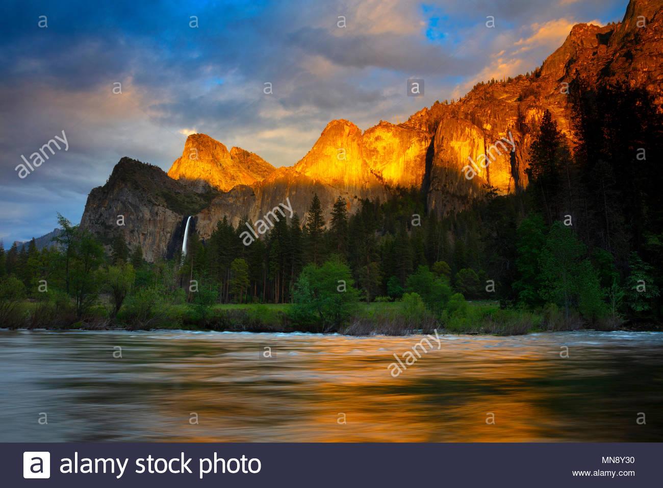 La luce dorata del tramonto si riflette diversi picchi di Yosemite, compresa la Torre Pendente e Dewey punto, sul fiume Merced a valle vista in Y Immagini Stock