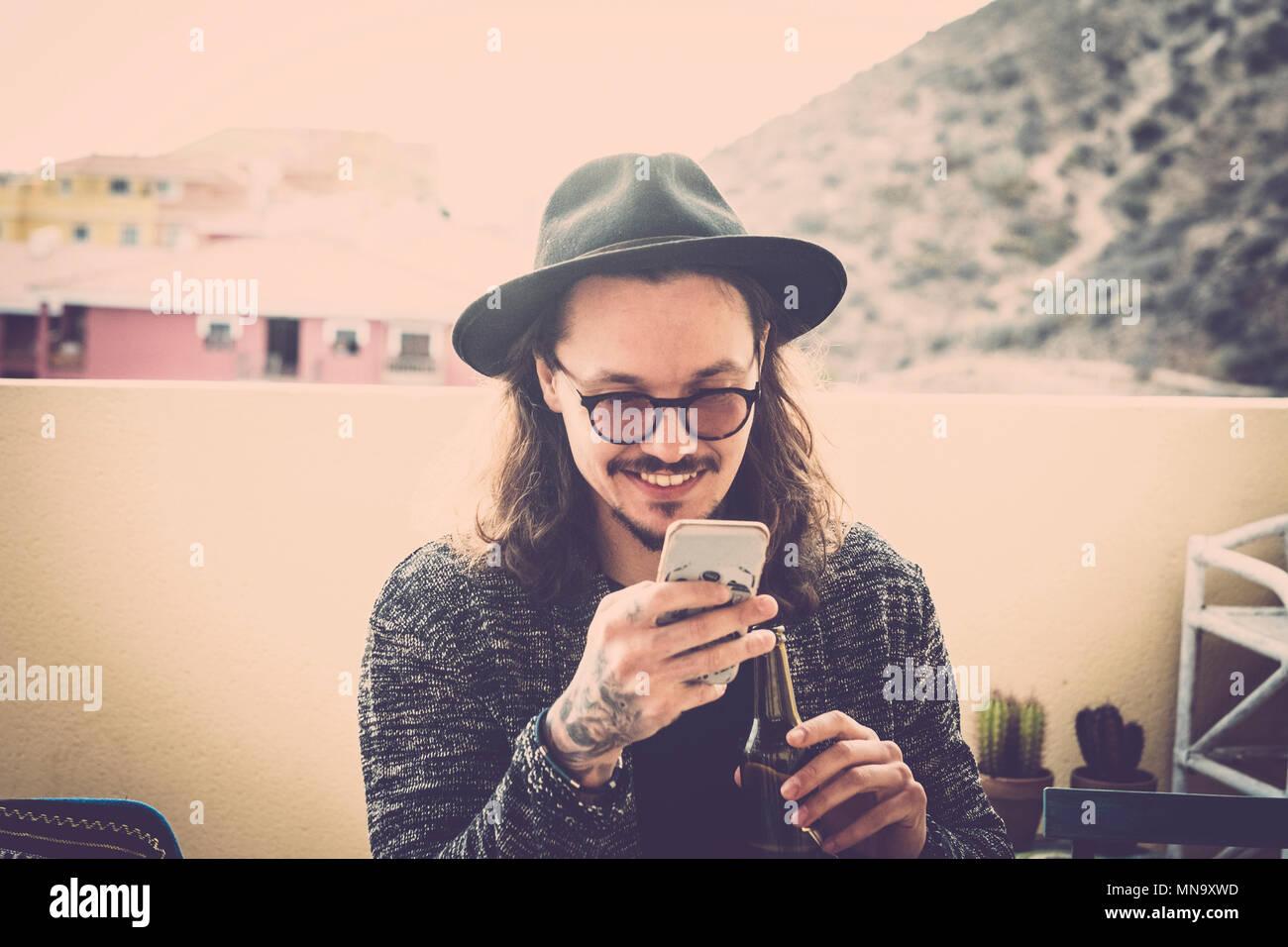 Capelli lunghi bella giovane uomo leggere e controllare il telefono sul roofteop terrazza all'aperto. cappello nero e occhiali e tatuaggio sulla mano. moda modello nic sith Immagini Stock