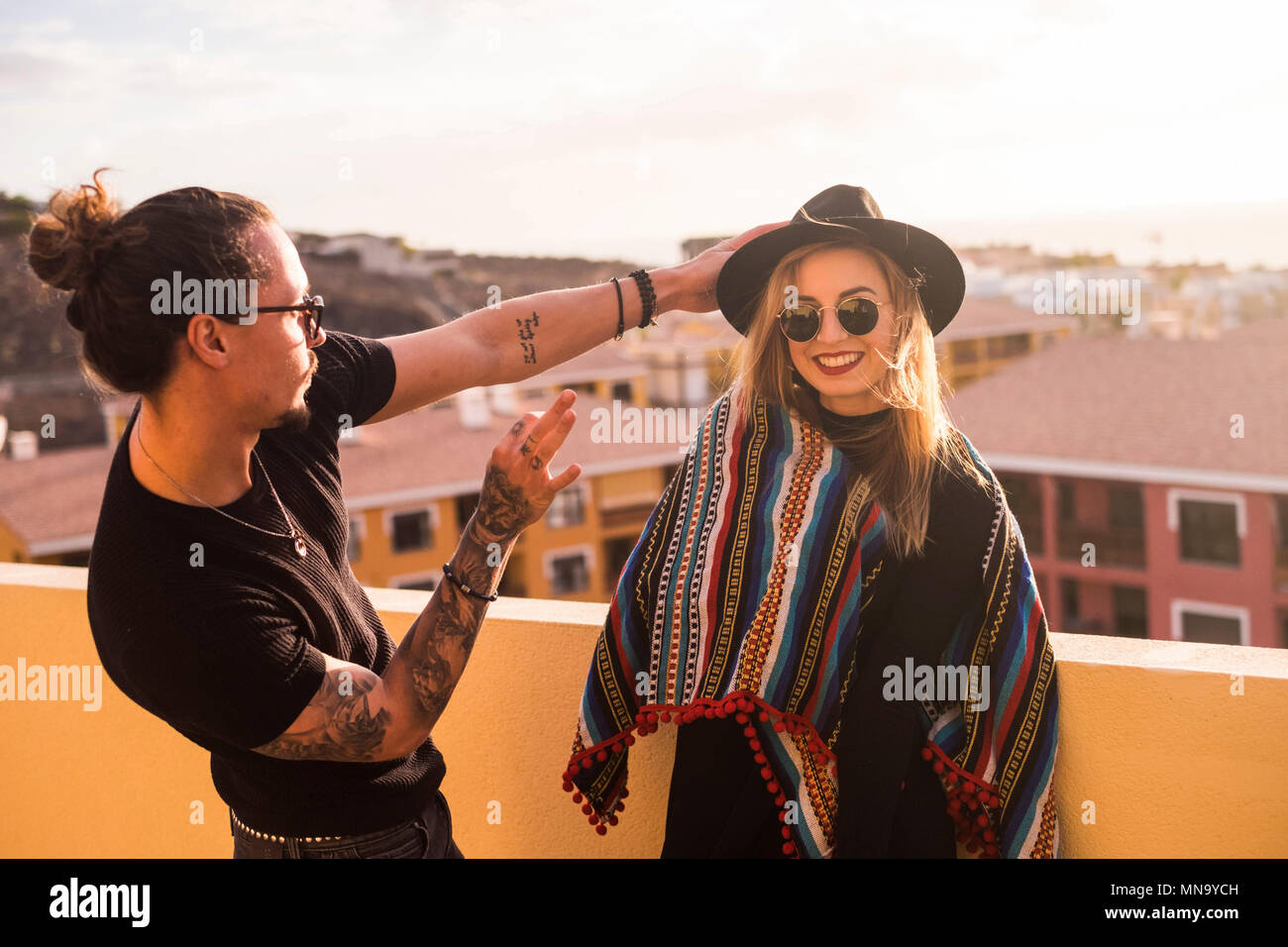 Bella coppia di amici del modello in rapporto a divertirsi sulla terrazza sul tetto di casa con incredibile vista su altre case e panorama. Ha un sorriso Immagini Stock