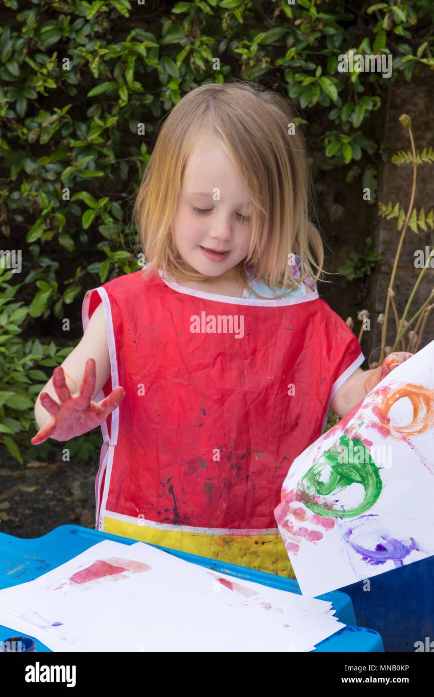 Due anni di pittura ragazza foto e disegni con vernici ad acquerello in giardino, ottenere vernice sulle mani. Abbigliamento protettivo. Immagini Stock