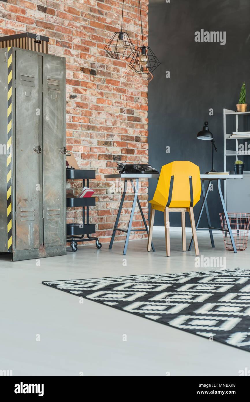 Industrial home office con un muro di mattoni e una libreria di metallo Immagini Stock
