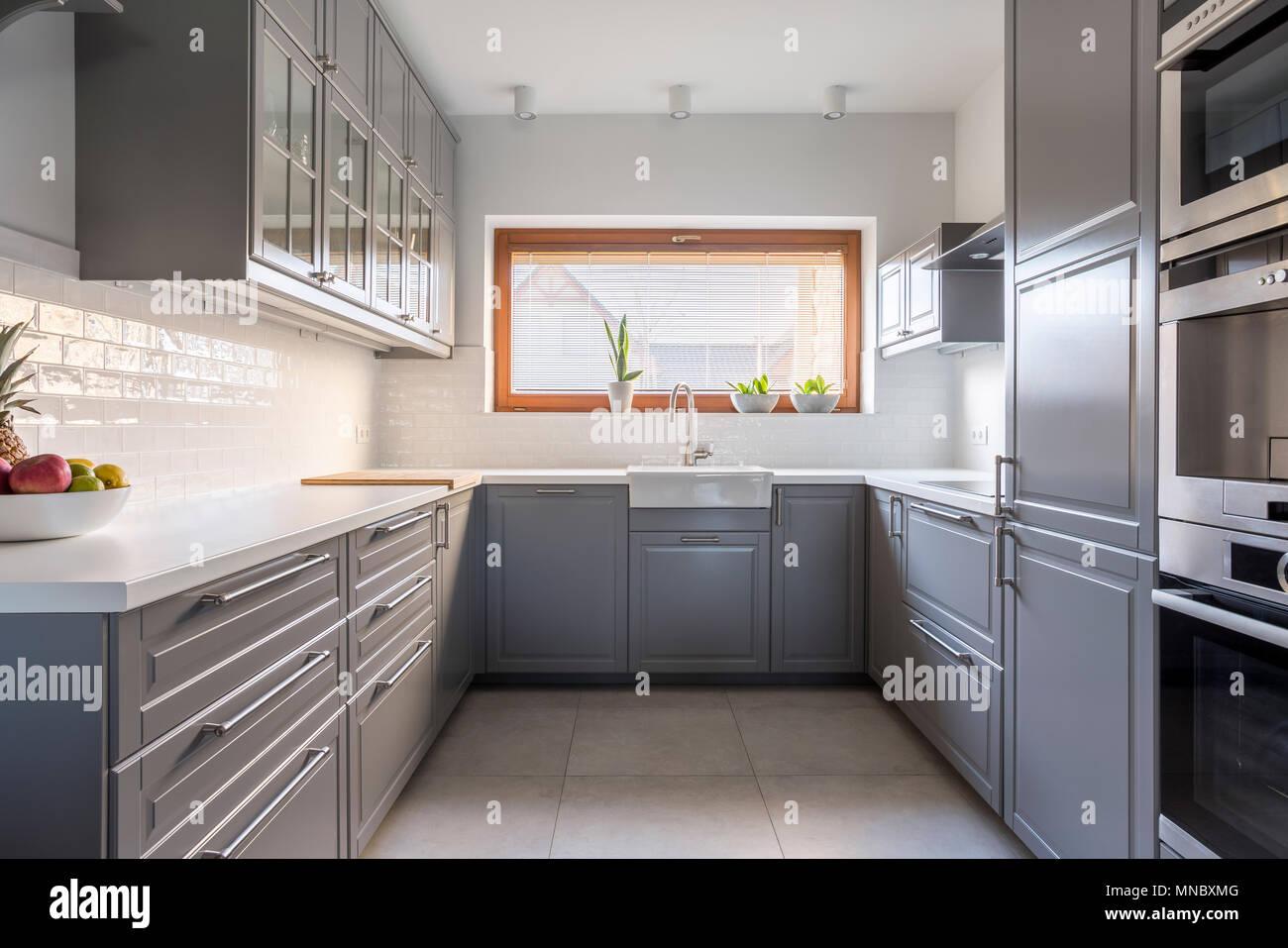 Luce cucina spaziosa con finestra e bianco delle piastrelle in