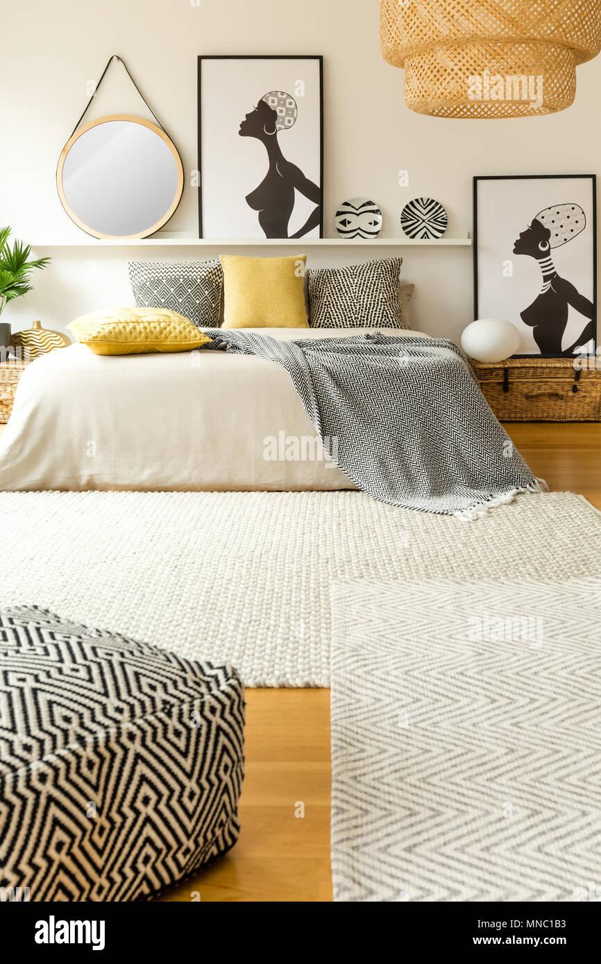 Pouf modellato vicino a letto con cuscini di colore giallo ...