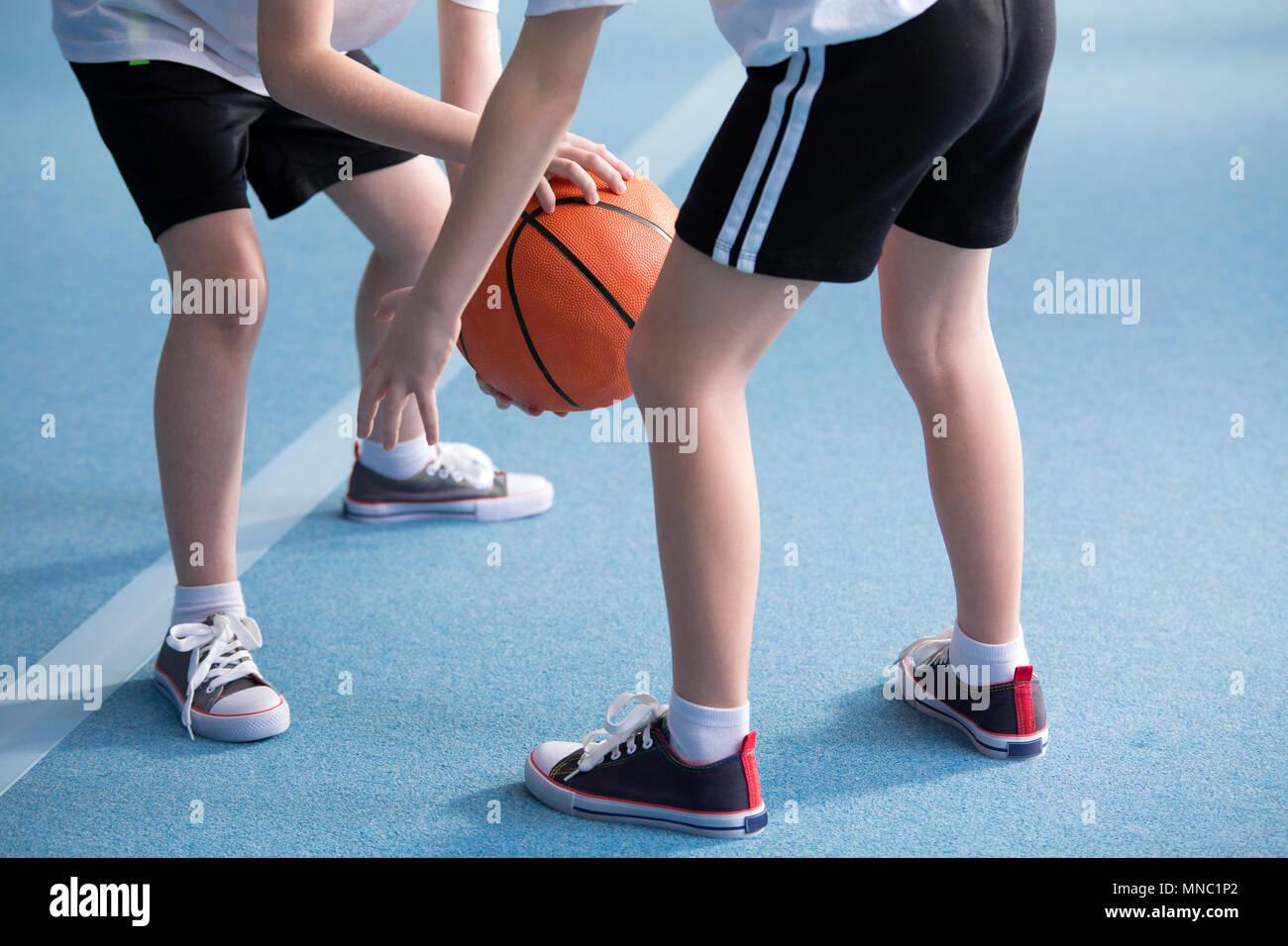 Close-up su giovani bambini indossare abbigliamento sportivo scuola imparare a sbavare un basket durante l'educazione fisica classi in palestra con pavimento di colore blu Foto Stock
