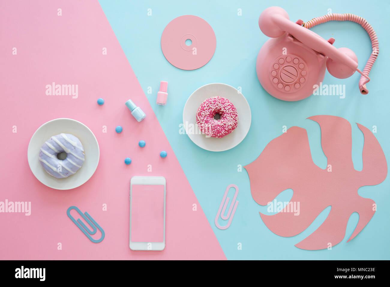 Rosa e blu nella tabella in alto di un blogger con un telefono, ciambelle, foglie di carta e cd Foto Stock