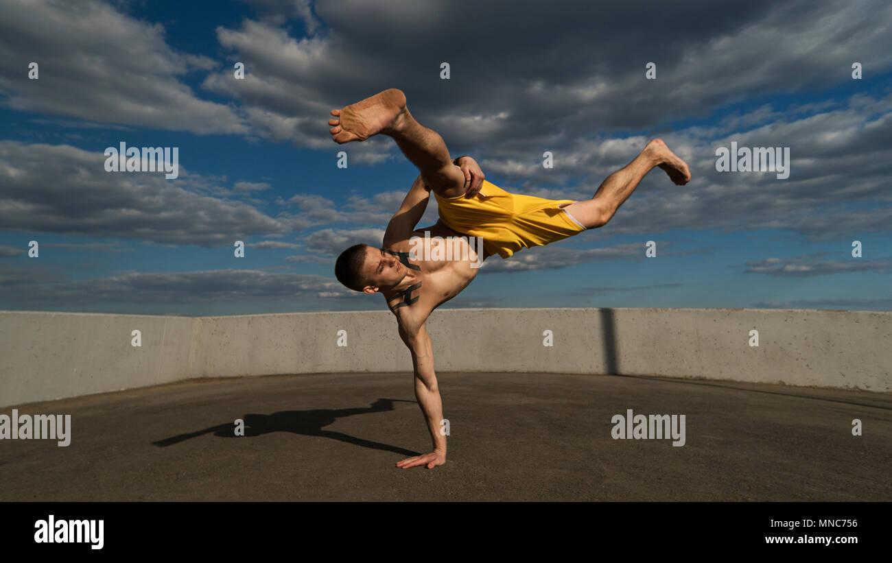 Ingannare sulla strada. Arti marziali. Uomo compie soffiare con supporto di sua mano a piedi nudi. Ripresi dal fondo scorcio contro sky. Immagini Stock