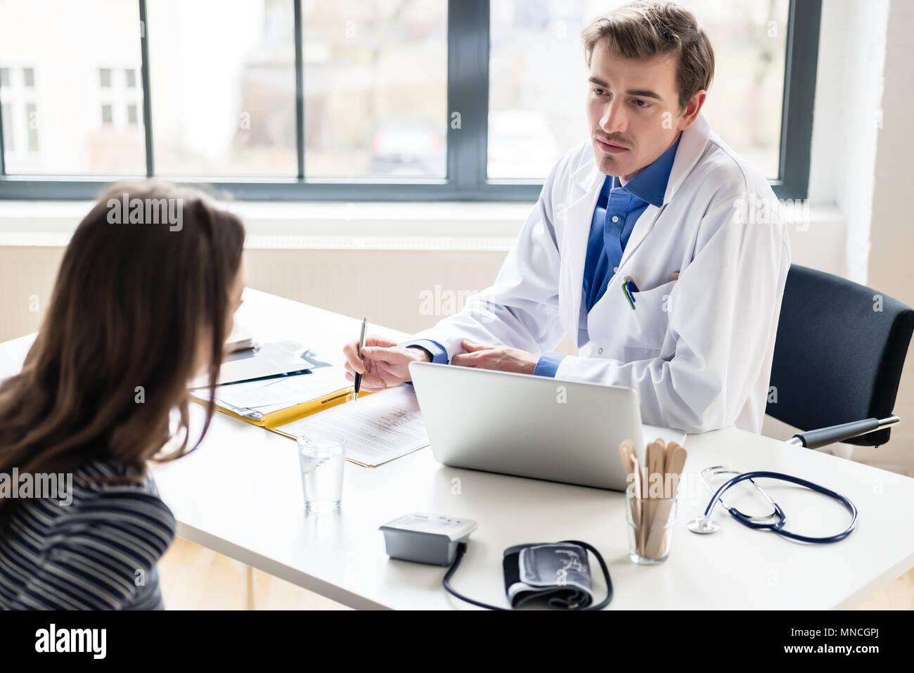 Giovane medico ascoltando la sua paziente con rispetto e dedizione Immagini Stock