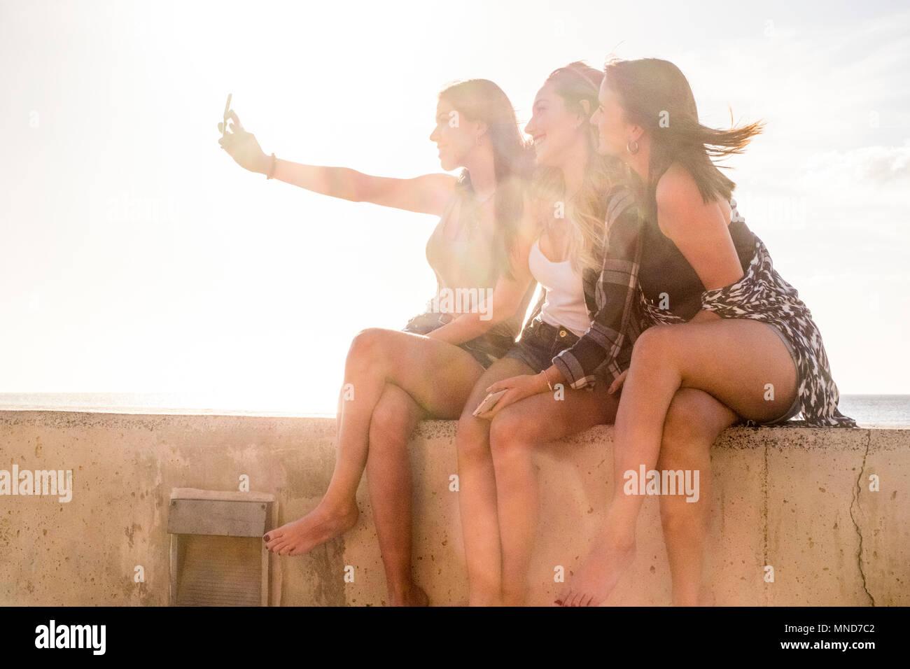 Un gruppo di tre donne in amicizia tenendo selfies e utilizzando il telefono vicino alla spiaggia in Tenerife. L'orario del tramonto, lotto di sorriso e felicità in vacanza. Bea Immagini Stock