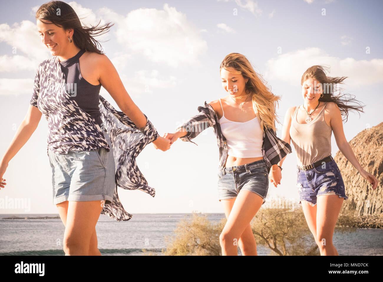 Tre giovani donne amici camminare insieme su un muro vicino alla spiaggia in Tenerife. Godetevi la vacanza sotto un cielo blu con sole giallo. Le mani con le mani. Immagini Stock