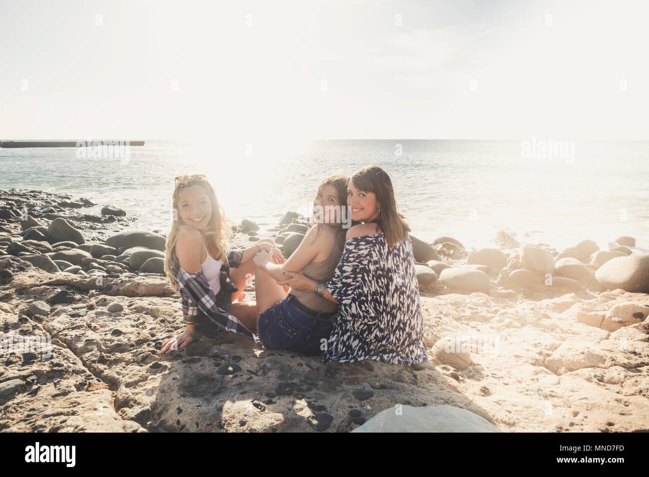 Gruppo di bella donna giovane che parla e sorridente attorno in una spiaggia di pietra in Tenerife. team ragazze divertirsi insieme Immagini Stock