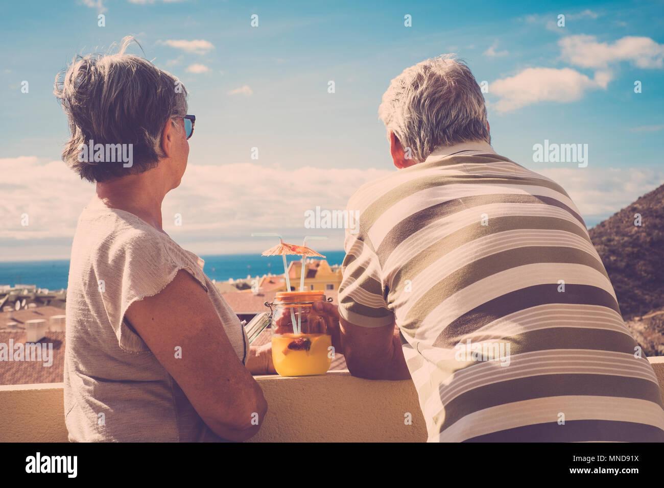 Due anziani uomo e donna guardando insieme la vista dell'oceano in vacanza. Vista posteriore con tetti in stile vintage. Immagini Stock