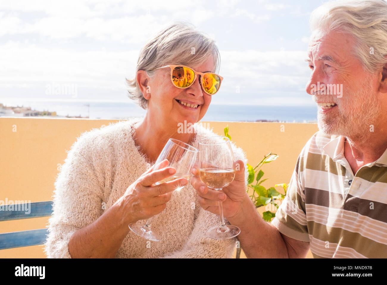 Coppia di anziani la tostatura con il vino in una terrazza esterna che si affaccia sul mare in estate Foto Stock