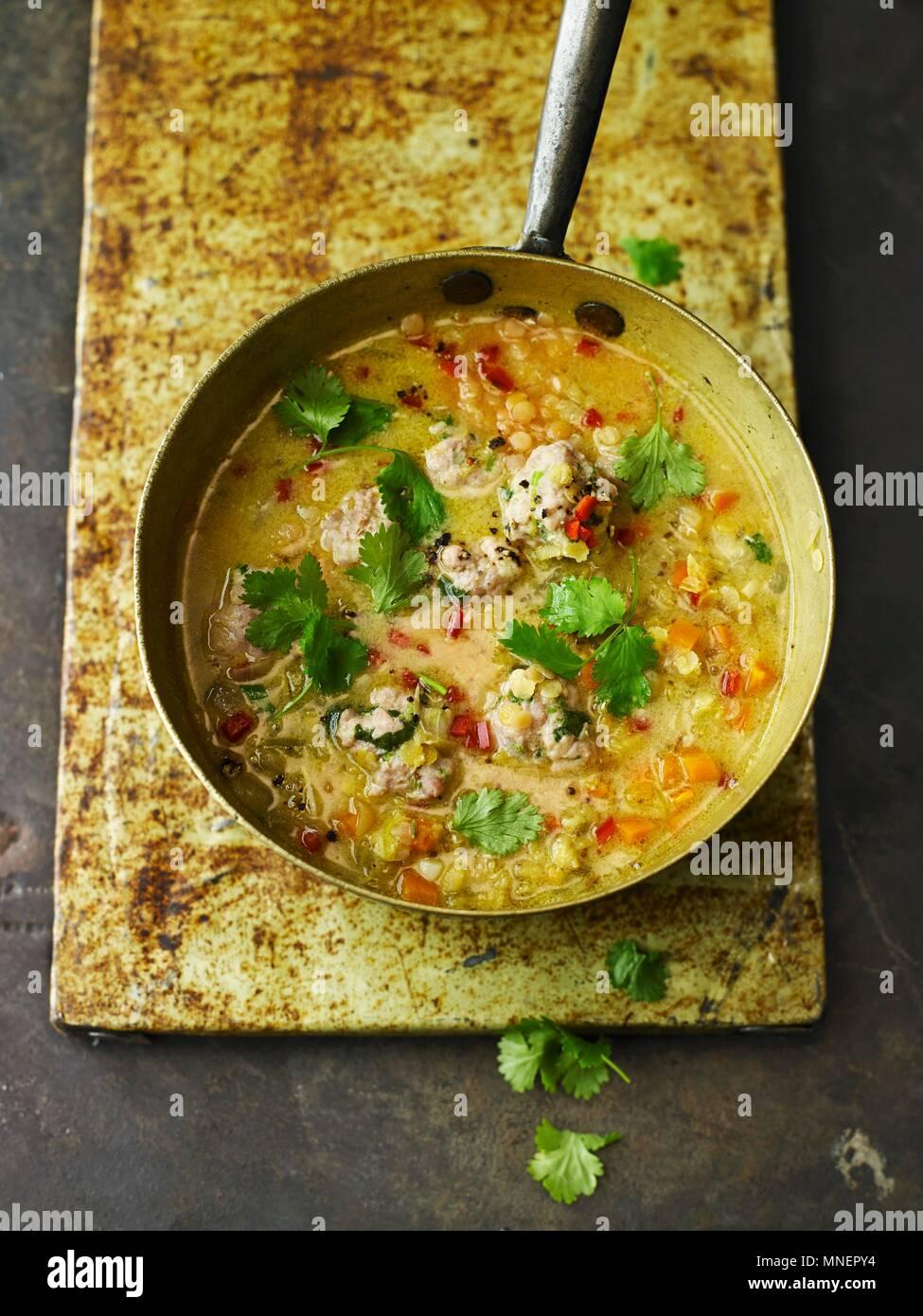 Spicy Red lenticchia, noce di cocco, e coriandolo zuppa con gnocchetti di pollo Immagini Stock