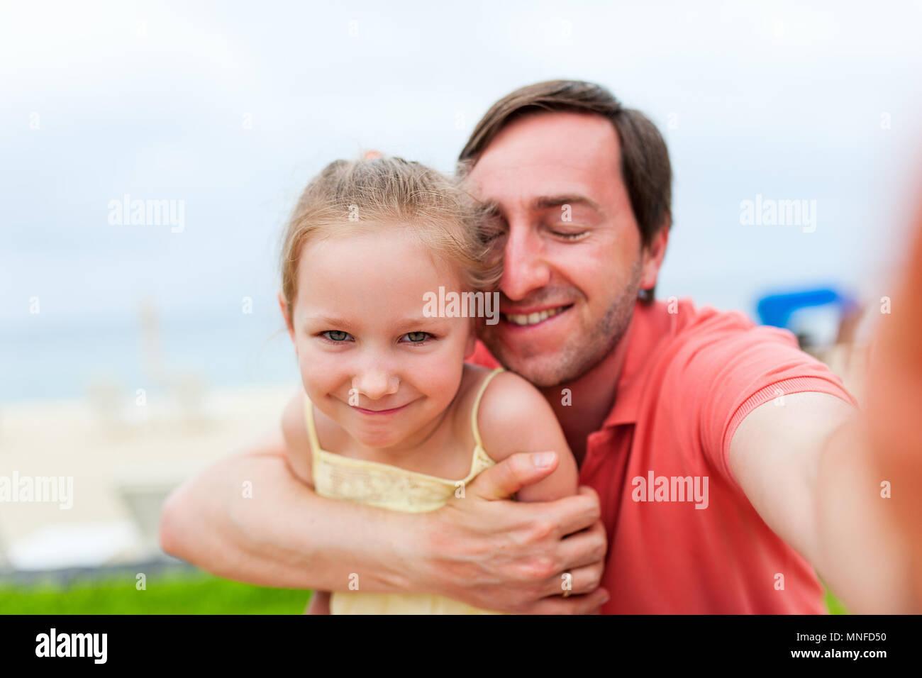 La famiglia felice padre e sua adorabile figlia piccola a beach tenendo selfie Immagini Stock