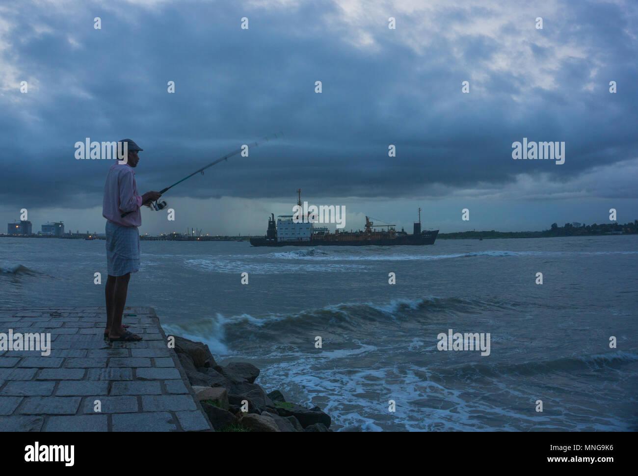 Un uomo pesca sportiva a Fort Kochi beachfront Immagini Stock
