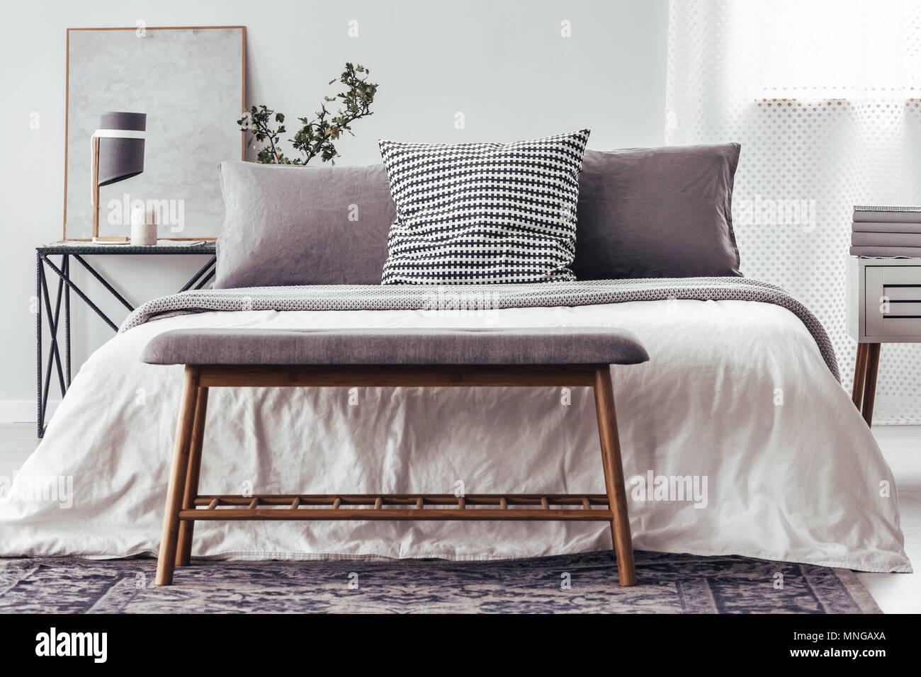 Close-up di panca di legno su un tappeto contro il letto bianco con ...