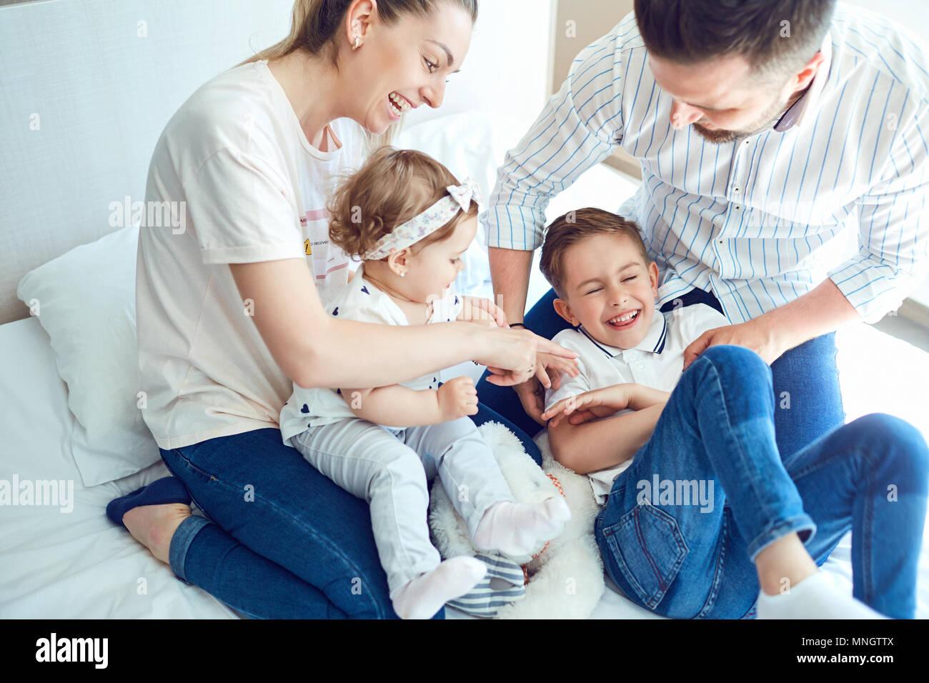 La famiglia felice giocando giacente sul letto in camera da letto. Foto Stock