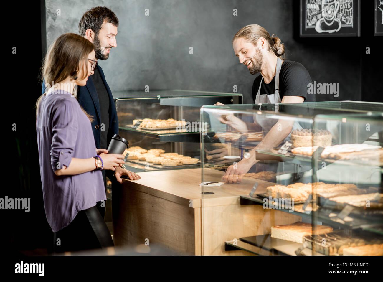 Coppia giovane acquisto di caffè in piedi con la bella barista nella moderna caffetteria Immagini Stock
