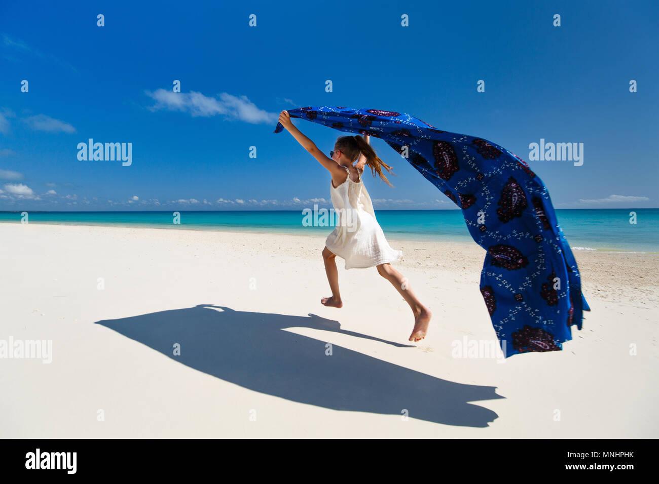 Carino bambina divertendosi in esecuzione con sarong e godersi la vacanza in spiaggia tropicale con sabbia bianca e mare turchese acqua Immagini Stock