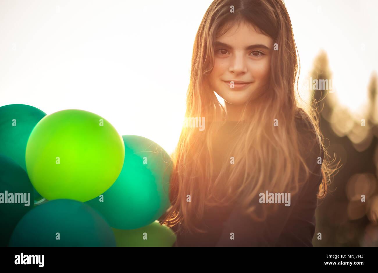 Ritratto di una ragazza carina con aria palloncini all'aperto in serata dolce della luce del sole, festeggia il compleanno, vacanze e concetto di divertimento Foto Stock