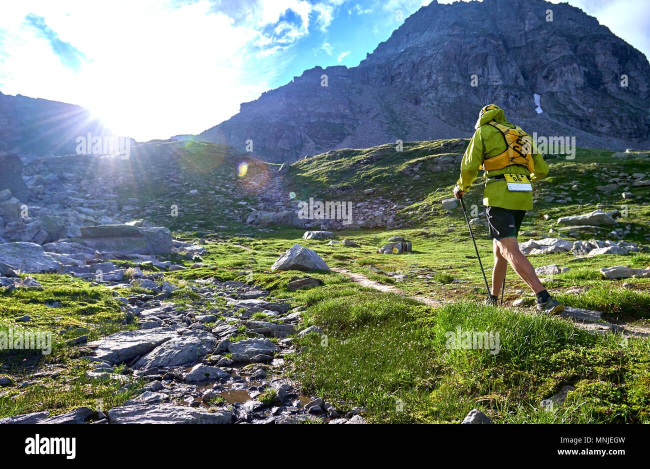 Vista posteriore del trail runner a camminare su ripido sentiero di montagna, Alpe Devero, Verbania, Italia Immagini Stock