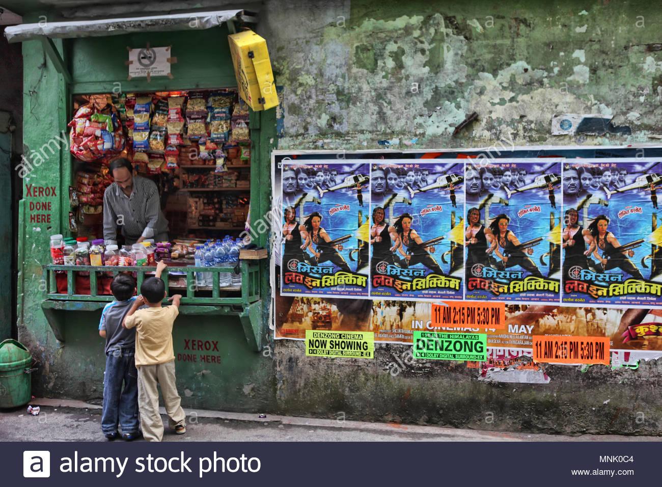 Due ragazzi acquistare dolci da un piccolo negozio di Gangtok, Sikkim, India. Intonacata sulla parete accanto al negozio sono i manifesti per il film 'Mission amore in Sikki Immagini Stock