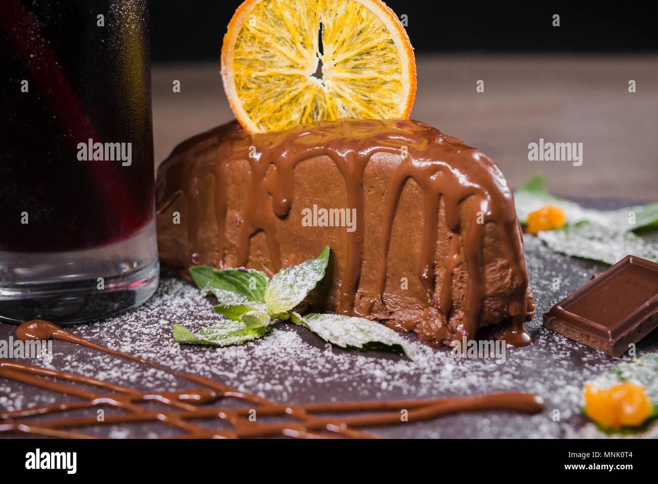 Dolce al cioccolato con scaglie di colore arancione su uno sfondo di legno Immagini Stock