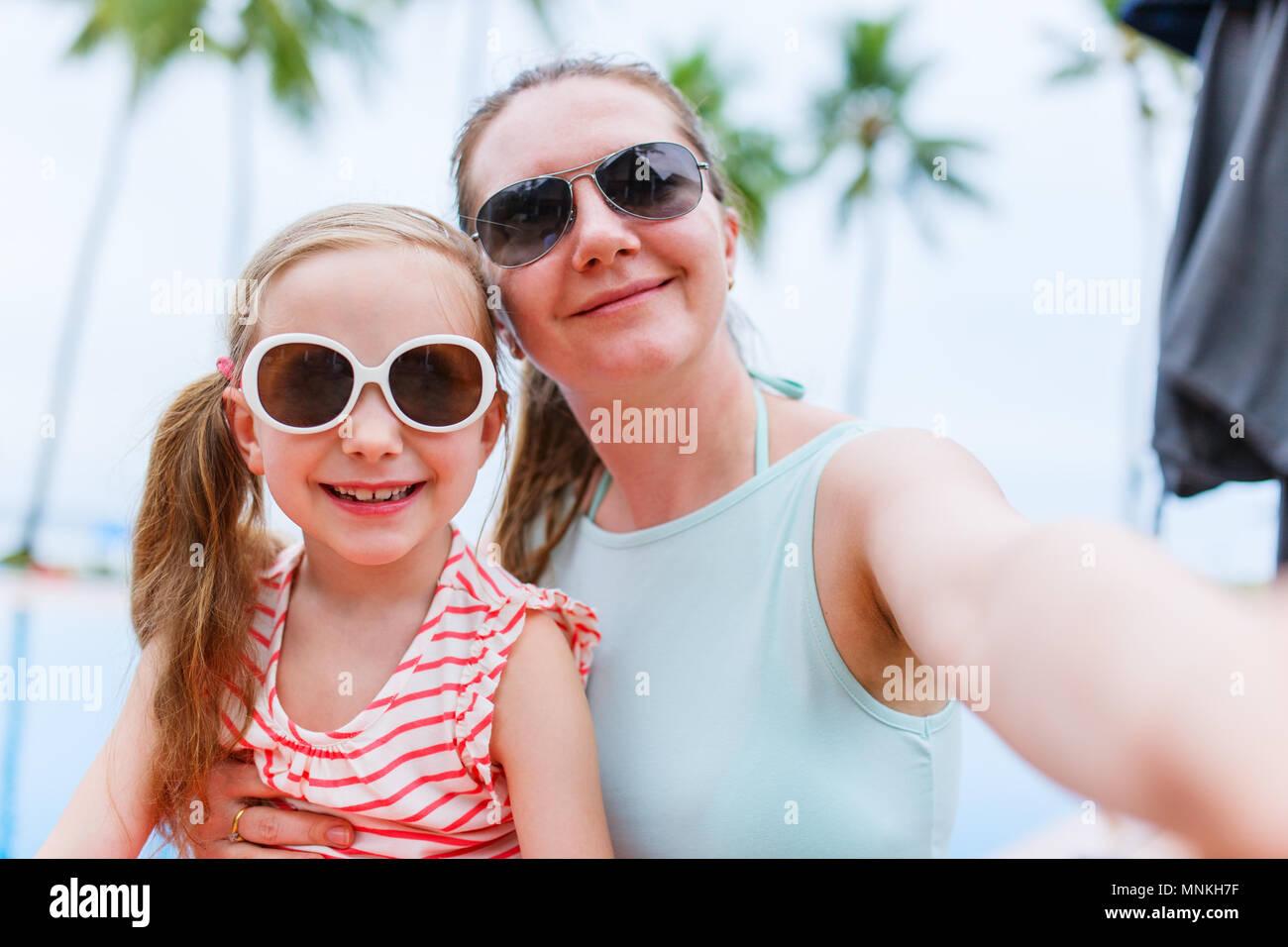 La famiglia felice la madre ed i suoi adorabili poco figlia sulle vacanze estive tenendo selfie con lo smartphone Immagini Stock