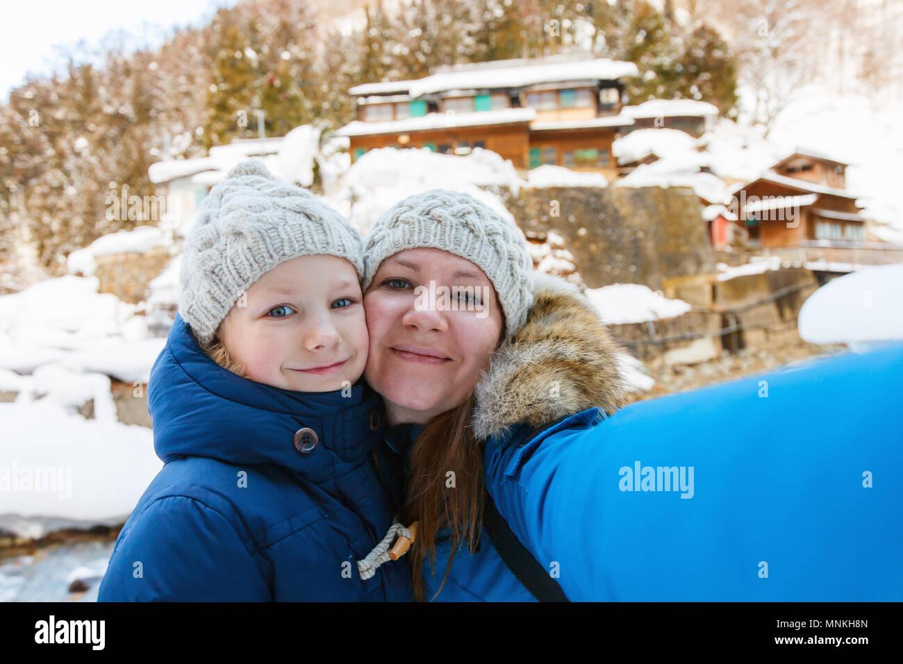 Madre e doughter tenendo selfie sulla bellissima giornata invernale all'aperto Immagini Stock