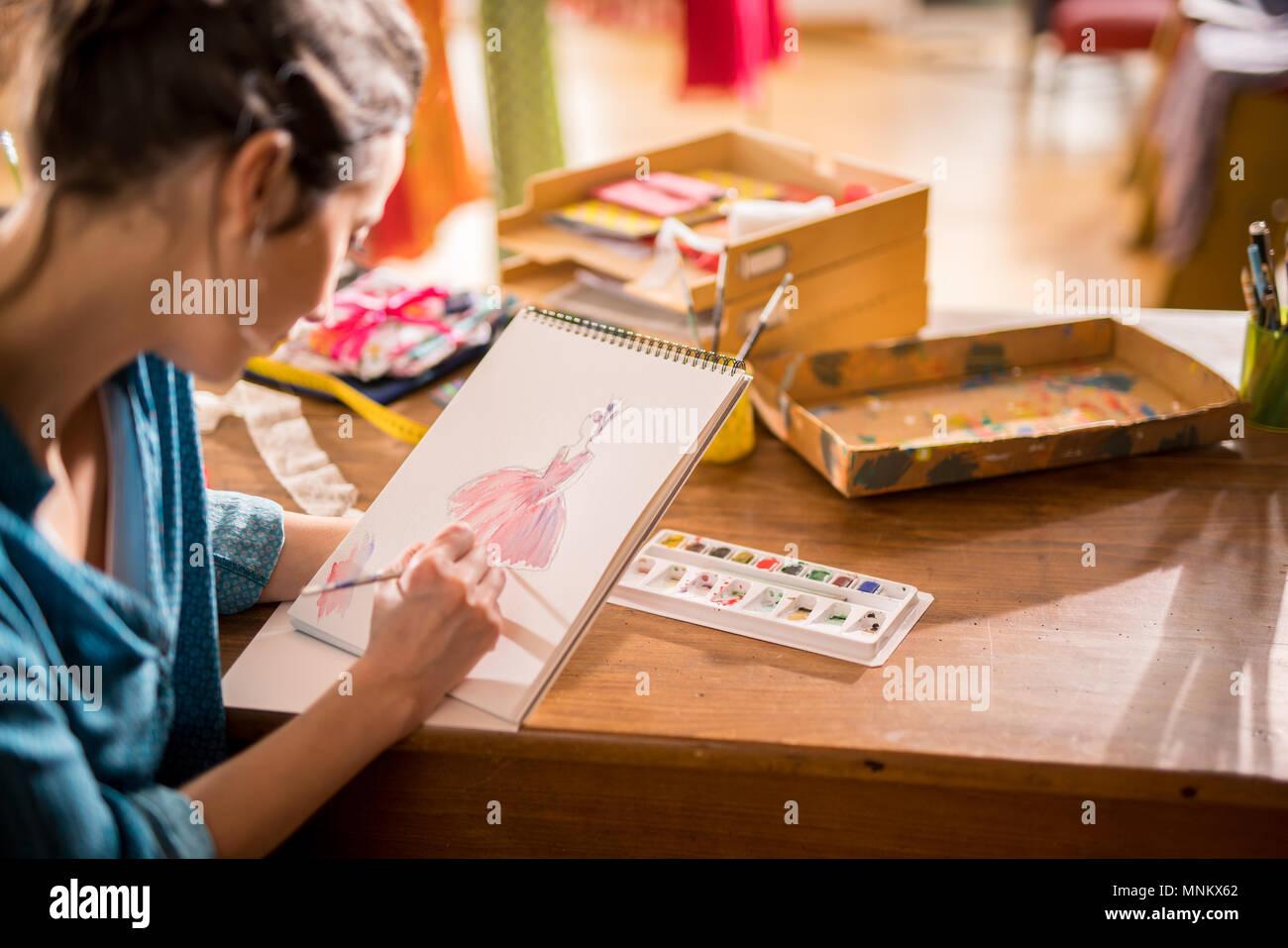 Fashion designer che lavora su un nuovo modello nel suo studio Foto Stock