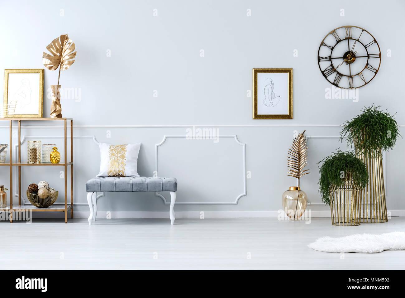 Ripiano in metallo grigio sgabello e piante in vasi d oro in