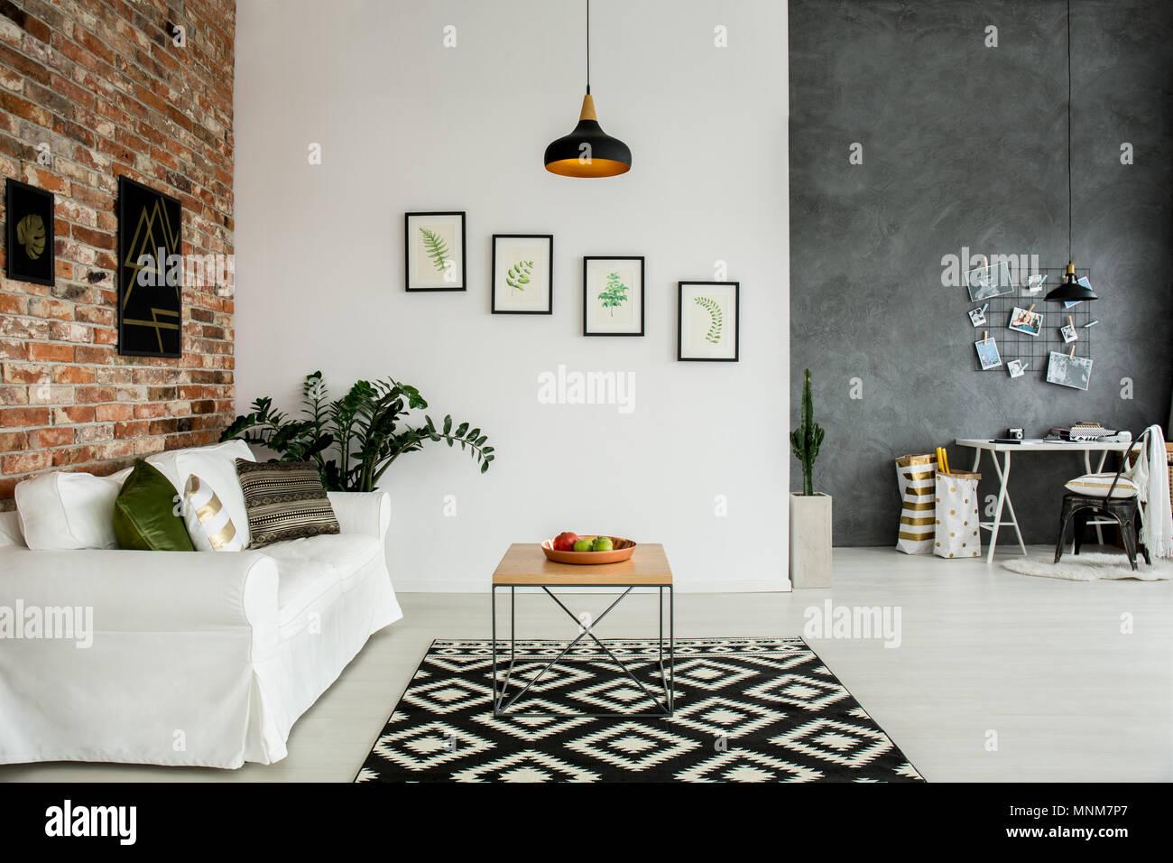 Soppalco interno con soggiorno aperto e semplice home office Immagini Stock